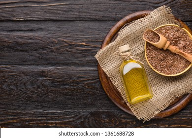 Linseed oil and bottle of linseeds on board over wooden background, top view, copy space