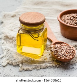 Linseed oil and bowl of linseeds on board on concrete background. Healthy oils concept