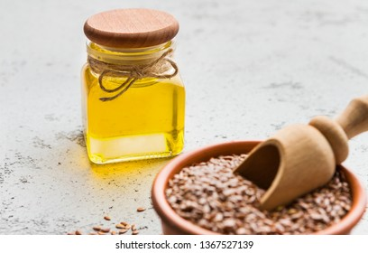 Linseed oil and bowl of linseeds on concrete background. Extra virgin oil concept