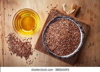 Linseed oil and bowl of linseeds on  wooden background. Top view