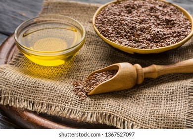 Linseed oil, bowl and scoop of linseeds on board over wooden background. Alternative medicine concept