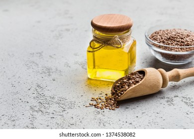 Linseed oil, bowl and scoop of linseeds on concrete background, copy space. Essential oils concept
