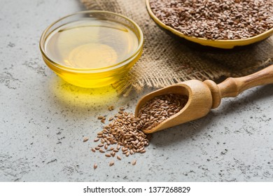 Linseed oil, bowl and scoop of linseeds on concrete background. Healing seeds concept