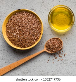 Linseed oil, bowl and spoon of linseeds on concrete background, top view. Omega 3 fatty acid concept
