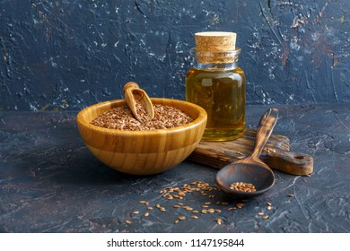 Linseed oil and flax seeds in a bowl and a wooden spoon on a dark textured background.