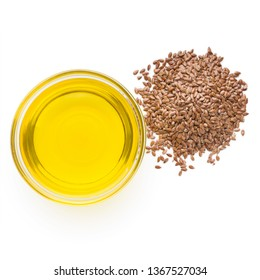 Linseed oil in glass bowl and heap of linseeds isolated on white background, top view. Omega 3 daily dose concept