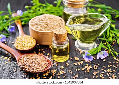 Linseed oil in two glass jars and a gravy boat with white and brown flax seeds in spoons, flour in a bowl, leaves and flowers on black wooden board background