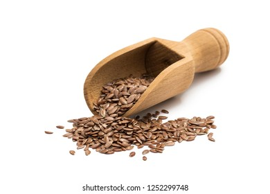 Linseeds or flax seeds on a wooden scoop or spoon from the front isolated on white background