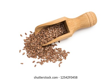 Linseeds or flax seeds on a wooden scoop or spoon seen almost directly from above isolated on white background