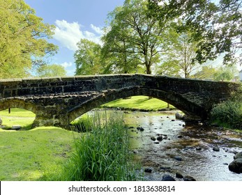 Linton bridge, spanning the Beck, with grass banks, and trees, in the heart of Linton, Skipton, UK