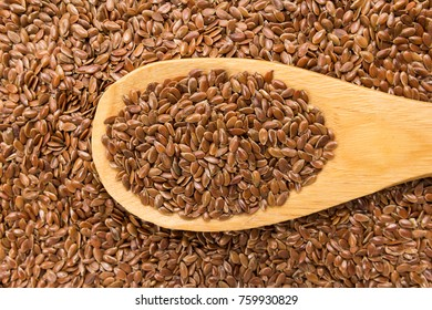 Linum usitatissimum is scientific name of Brown Flax seed. Also known as Linseed, Flaxseed and Common Flax. Grains in wooden spoon. Close up.