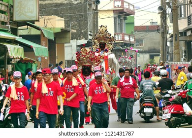 LINYUAN, TAIWAN -- MAY 28, 2017: Member of a religious temple carry effigies of deities through the narrow streets.