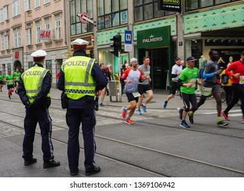 LINZ, AUSTRIA - APRIL 14, 2019: The Linz Donau Marathon. Two police men are looking at the marathon and watching the race. The police officer controls the security, and makes sure that is safe to run.