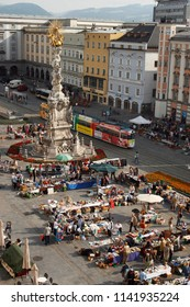 LINZ, AUSTRIA – JUNE 20, 2008: unidentified men and women sit and walk at the flea market in the Main Square on June 20, 2008 in Linz, Austria