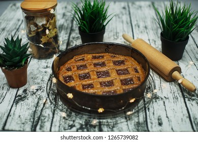 Linzer torte (christmas almond pastry with lattice design) and a cookie jar on a decorated wooden table.