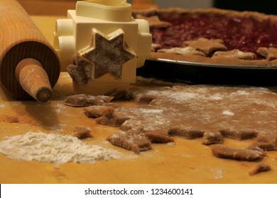 Linzer Torte (Linzertorte). Rolled dough with rolling pin and cookie cutter as a star. Raw dough in a brook shape decorated with raspberry jam and stars. The process of making pie dough by hand.