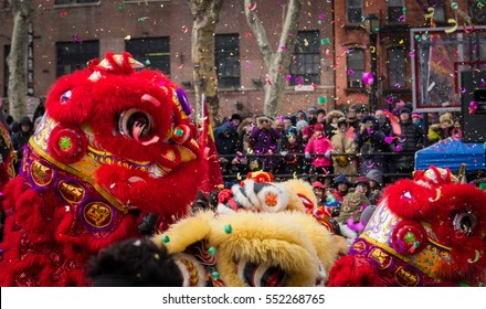 Lion dance and confetti in a crowded celebration of Chinese New Year in Chinatown, New York.