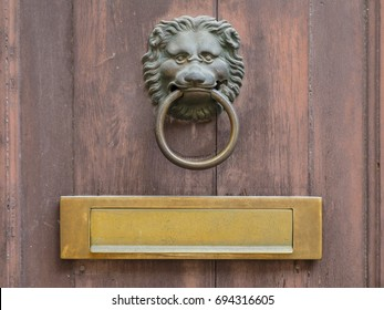 Lion face shape door knocker and letterbox on ancient wooden door