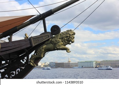 Lion Figurehead at the Prow of Old Vintage Naval Ship Moored in St. Petersburg, Russia. Carved Figurehead Decoration with Lion Sculpture on Cloudy Sky Background. Naval and Marine Old Ship Details.