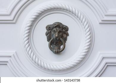Lion head door knocker on the white door