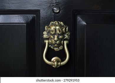 Lion head door knocker on a black door