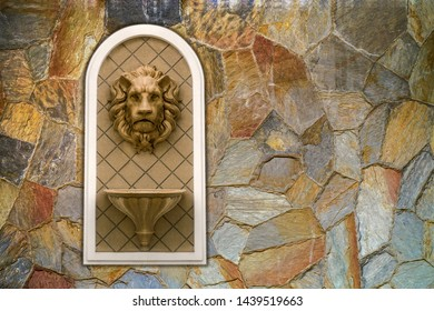 Lion head statue on cavernous stone wall. concept decoration architecture sculpture low relief ornament. decoration crest symbol animal waterspout fountain front view.