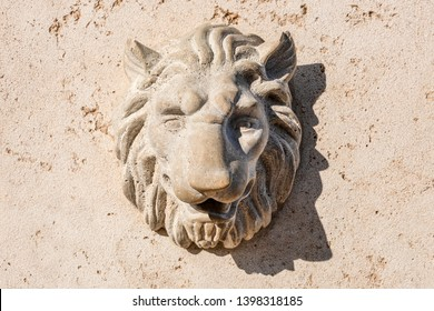 Lion head statue on natural cavernous stone wall - concept decoration architecture sculpture low relief ornament decoration crest symbol animal wildlife waterspout fountain front view background