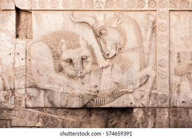 A lion hunting a bull,Bas relief sculpture carving on a wall.  Persepolis,Shiraz,Iran.