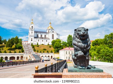 Lion sculpture on Pushkin bridge and Assumption cathedral in Vitebsk, Belarus with dramatic sky and shallow depth of field