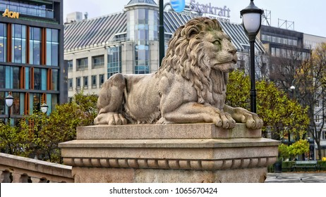Lion statue close to the Parliament of Norway. Stone sculpture of a lion with buildings in the background. Norway, Oslo - November 4, 2017