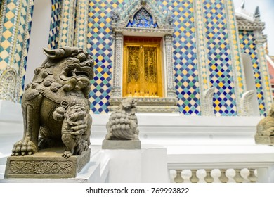 A lion statue stands outside a temple at Wat Phra Kaew, Bangkok, Thailand