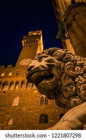 Lion status looks below the clock tower of the town hall in Florence during a beautiful evening