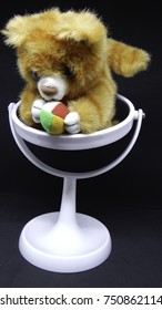 Lion toy with colorful ball in his paws sitting on white mirror on black background