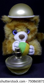 Lion toy with a colorful ball and perfume cover on his head and perfume bottle stanidng in front of him on black background, beauty composition
