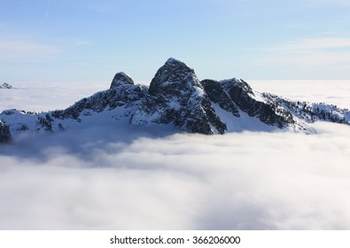 The Lions above the clouds in North Shore Mountains, BC, Canada. These mountains can be seen from many locations around Vancouver and they stand as landmarks.