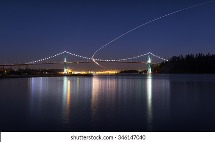 The Lions Gate Bridge at night from West Vancouver with a light trail from a helicopter.