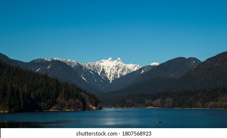 The Lions seen from Cleveland Dam at Capilano Lake. North Vancouver, BC, Canada.