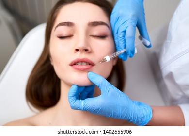 Lip Augmentation. Closeup Of Beautician Doctor Hands Doing Beauty Procedure To Female Lips with Syringe. Young Woman's Mouth Receiving Hyaluronic Acid Injection. Cosmetology Treatment. Filler Therapy.
