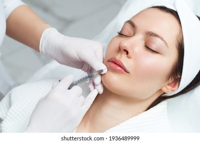 Lip augmentation and correction procedure in a cosmetology salon. The specialist makes an injection in the patient lips.