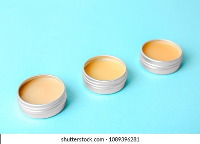 Lip balms on color background, closeup