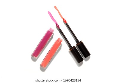 Lip glass liquid stick isolated on white with strong harsh shadows product for magazine layout pink and orange color