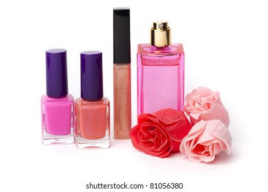 Lip gloss, perfume, nail polish bottles and rose flowers on white background