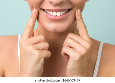 lip protection. close up of a young woman beautiful smile, healthy lips and white teeth on aqua-mint background
