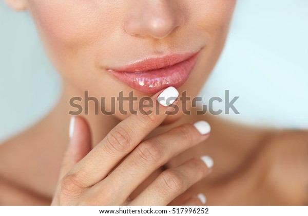 Lip Protection. Closeup of Beautiful Young Woman Healthy Lips. Female Model Mouth With Smooth Perfect Skin And Natural Manicure Touching Her Plush Lips. Lip Care And Beauty. High Resolution