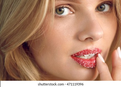 Lip Skin Care. Closeup Of Beautiful Young Woman With Fresh Beauty Face, Soft Pure Skin And Sweet Plump Full Lips Touching Cosmetic Sugar Lip Scrub On Her Lips. Cosmetics Concept. High Resolution Image