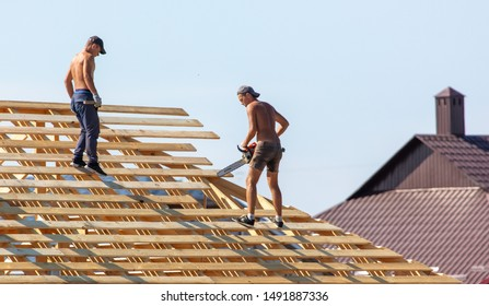 Lipetsk, Russia - August 30, 2019: Workers work with a tree on the roof of the house. Construction of the cottage.