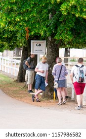 Lipica, Slovenia July 21st 2018. English tourists waiting by a sign of English language for a tour guide in Lipizzan stud farm. Tour Guide concept