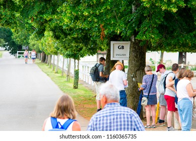 Lipica, Slovenia July 21st 2018. English tourists waiting by a sign of English language for a tour guide in Lipizzan stud farm. Tour Guide concept.