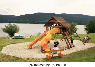 Lipno, Czech Republic - August 12, 2010. Children are playing on the plastic, wooden and rope playground in the meadow among mountains by lake. Lipno is a popular place for relax. Travel concept.