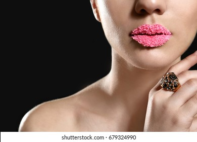 Lips of beautiful young woman covered with sugar on dark background, closeup